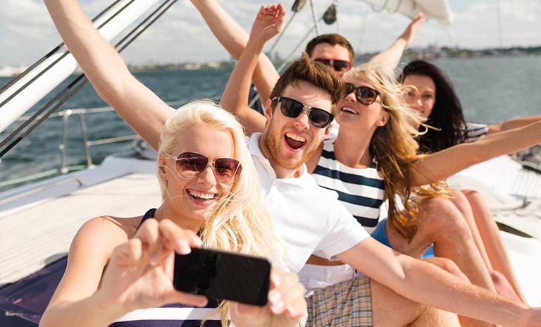 Grupo de amigos tomándose una selfie y teniendo una aventura en yate