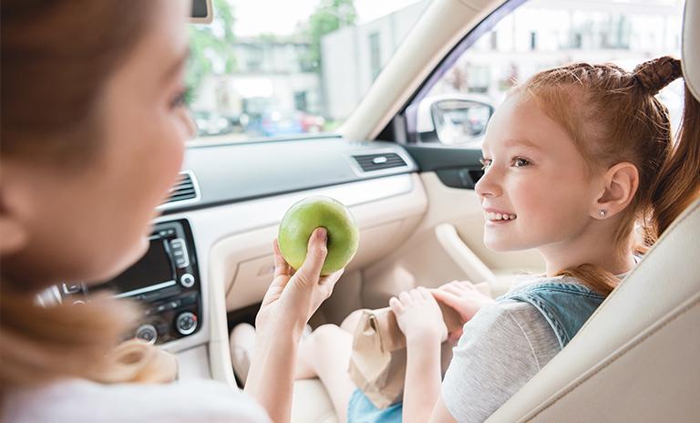 comiendo manzana en un carro seguro con una niña