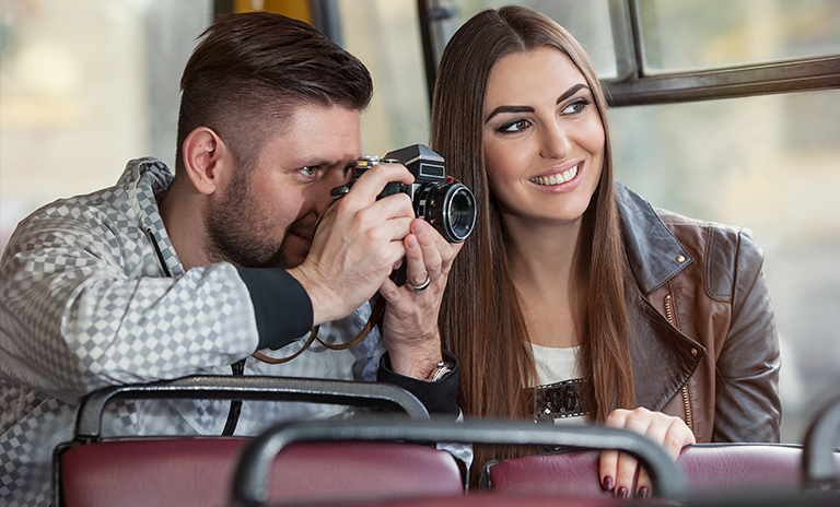 pareja fotografiando un lugar de su viaje