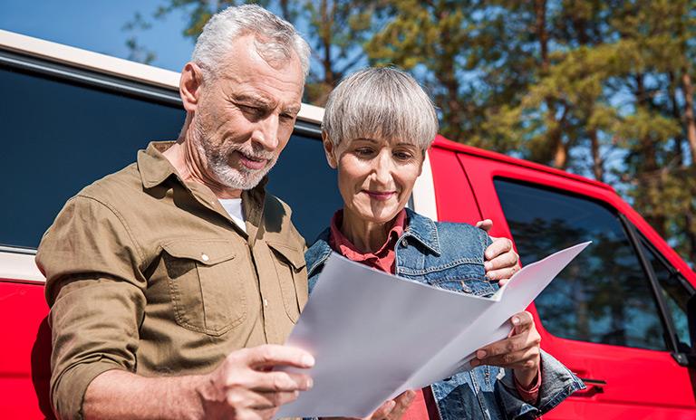 Una pareja de adultos mayores buscando su próximo destino en el mapa