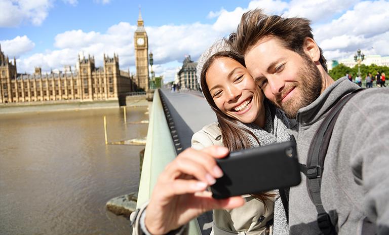 Una pareja haciéndose una selfie al borde de un puente