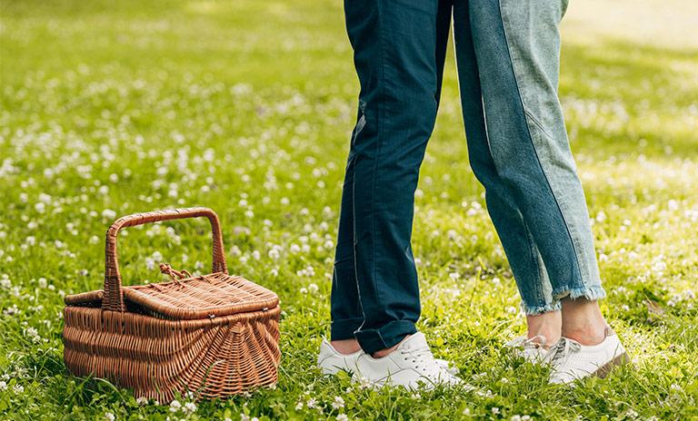 dos personas dándose un abrazo en medio de un picnic romántico