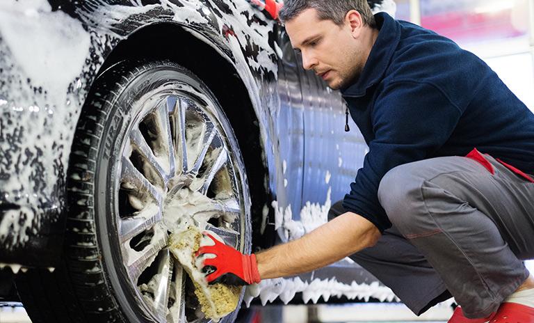 Hombre lavando carro uno de los beneficios de la comunidad Motorysa
