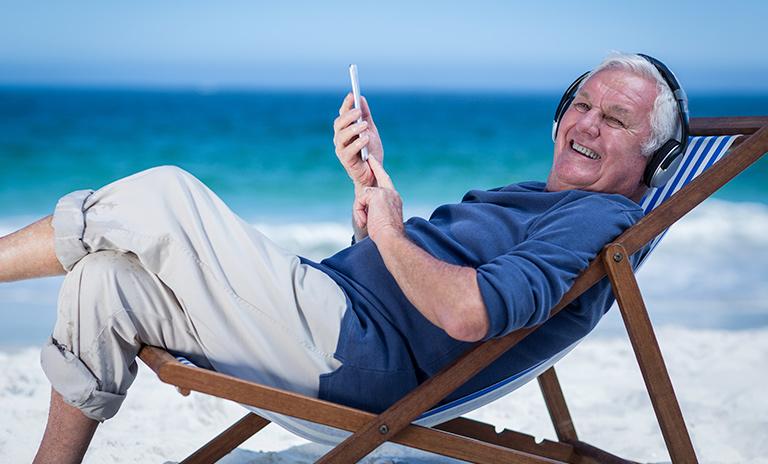 un hombre mayor escuchando música en su viaje a la playa