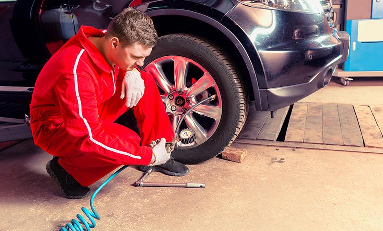 Mecánico revisando la presión de los neumáticos