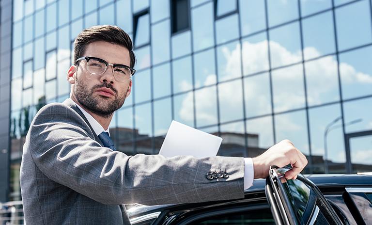 Hombre mirando al horizonte desde su carro nuevo