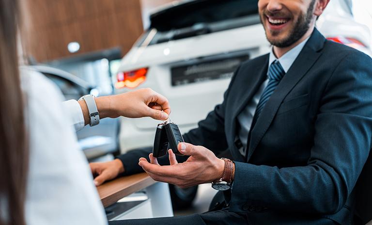 Hombre sonriendo porque le entregan las llaves de su carro nuevo