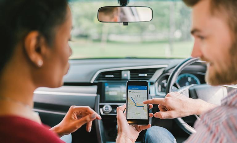 Pareja buscando ruta en aplicaciones de navegación GPS