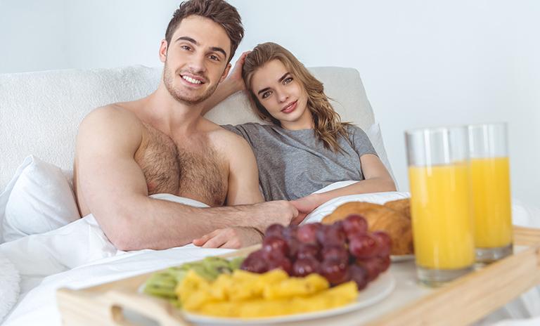 Pareja disfrutando un desayuno en cama