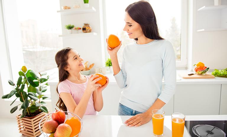 Madre e hija tomando jugo de naranja para el cuidado personal