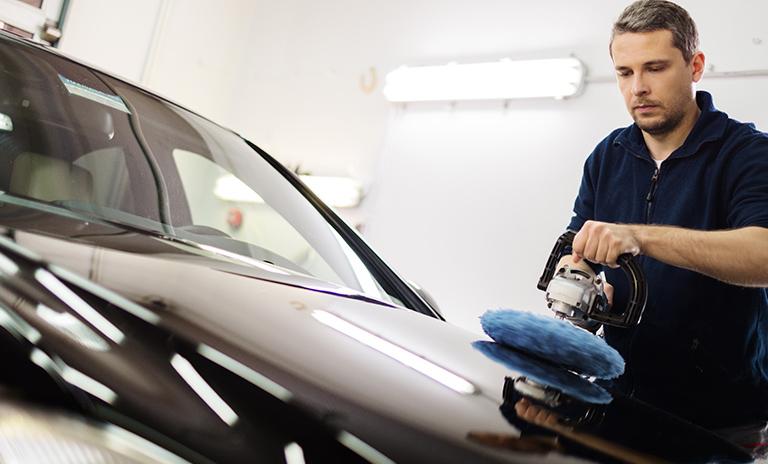 Hombre pule para cuidar la pintura del carro