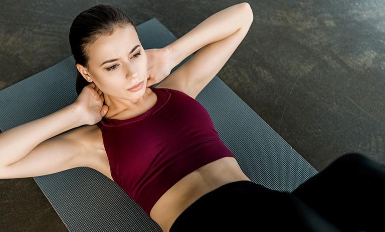 mujer haciendo rutina de abdominales como ejercicio en casa