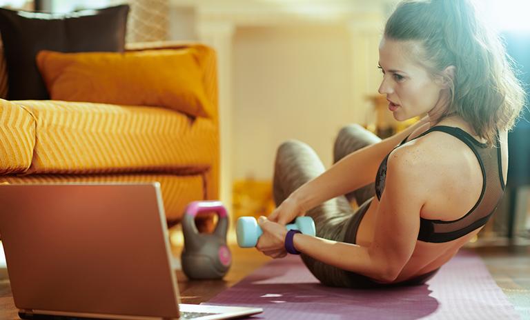 Mujer haciendo ejercicio en casa guiado por la pc