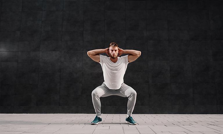 Hombre hace sentadillas contra la pared en casa