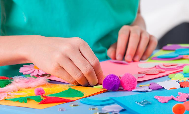 Niño sobre una mesa haciendo manualidades en casa