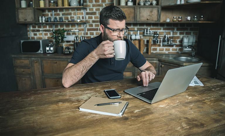 Hombre trabajando desde casa en su escritorio para mantener la productividad