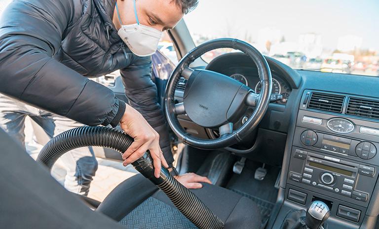 Hombre limpiando su vehículo de coronavirus con una aspiradora