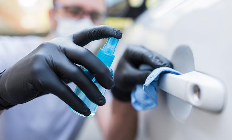 Hombre desinfectando las manillas de su vehículo
