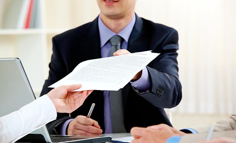 Persona entregando documento para refinanciar el vehículo