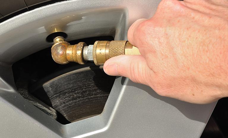 Hombre inflando las llantas de su auto