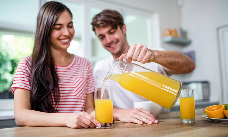 Pareja sirviendo un vaso de jugo de naranja