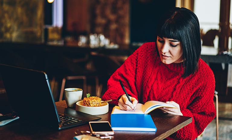Mujer escribiendo anotaciones de los cursos gratis para hacer en cuarentena