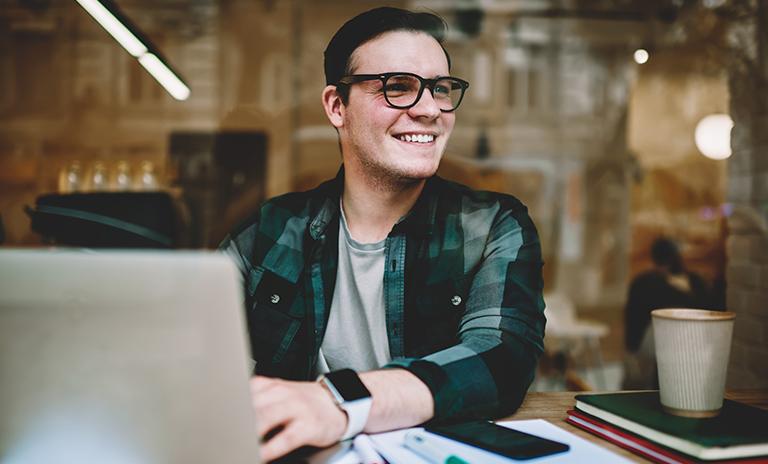 Joven hombre feliz por los cursos gratis para hacer en cuarentena