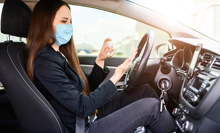 Mujer siguiendo las recomendaciones de bioseguridad para utilizar su vehículo.