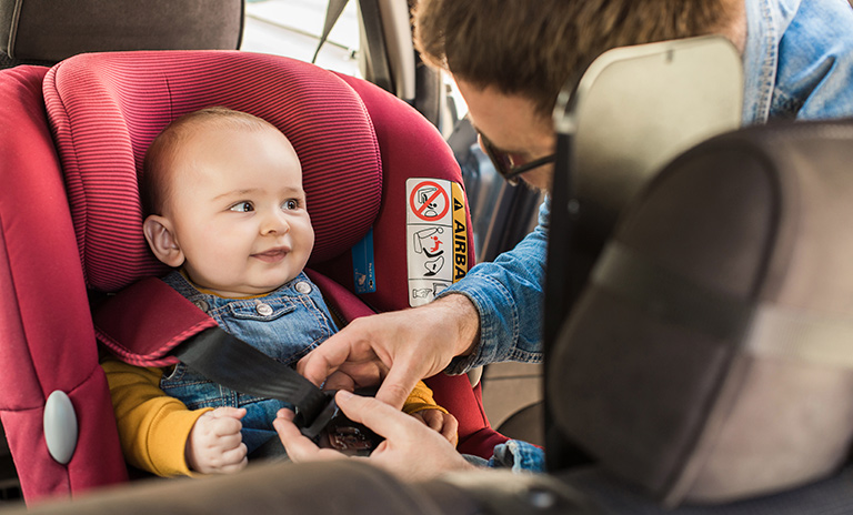 Padre ajustando la silla de bebé al sistema de sujeción infantil ISOFIX