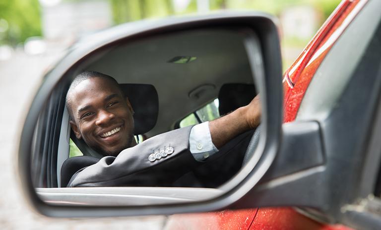 Hombre feliz mientras maneja para lidiar con los trancones de la ciudad