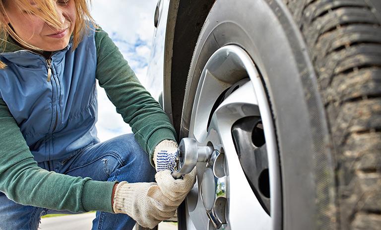 Mujer cambiando una llanta del auto